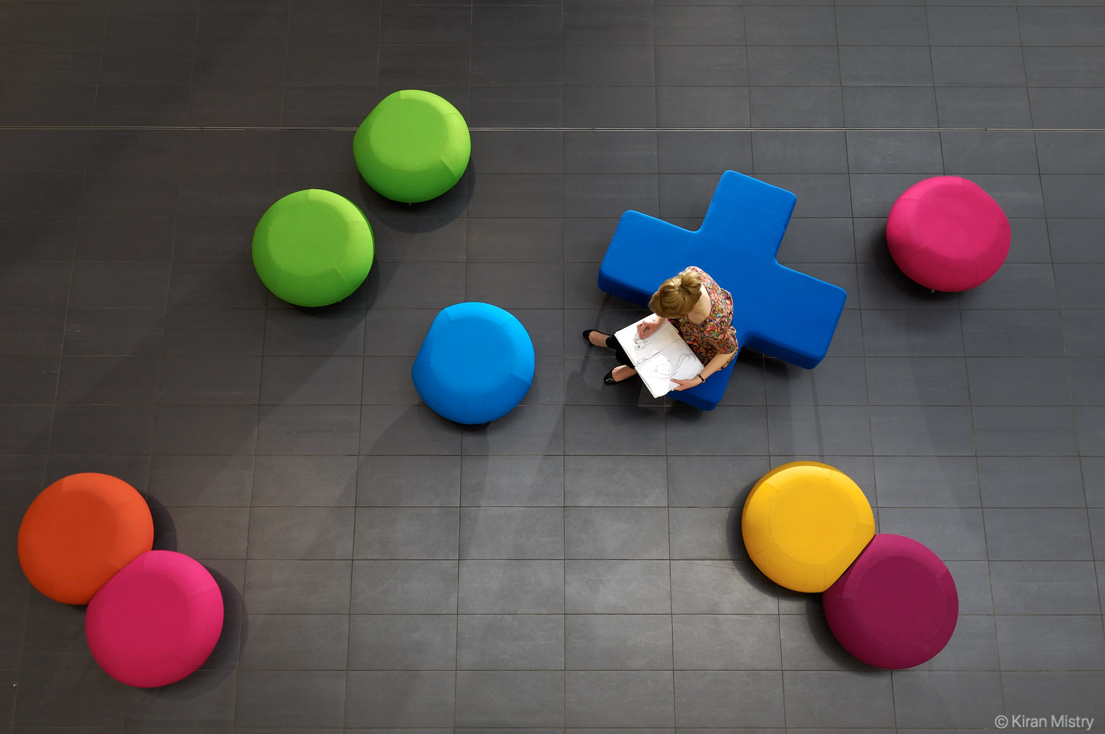 overhead view of college girl sat on colourful chairs sketching a portrait