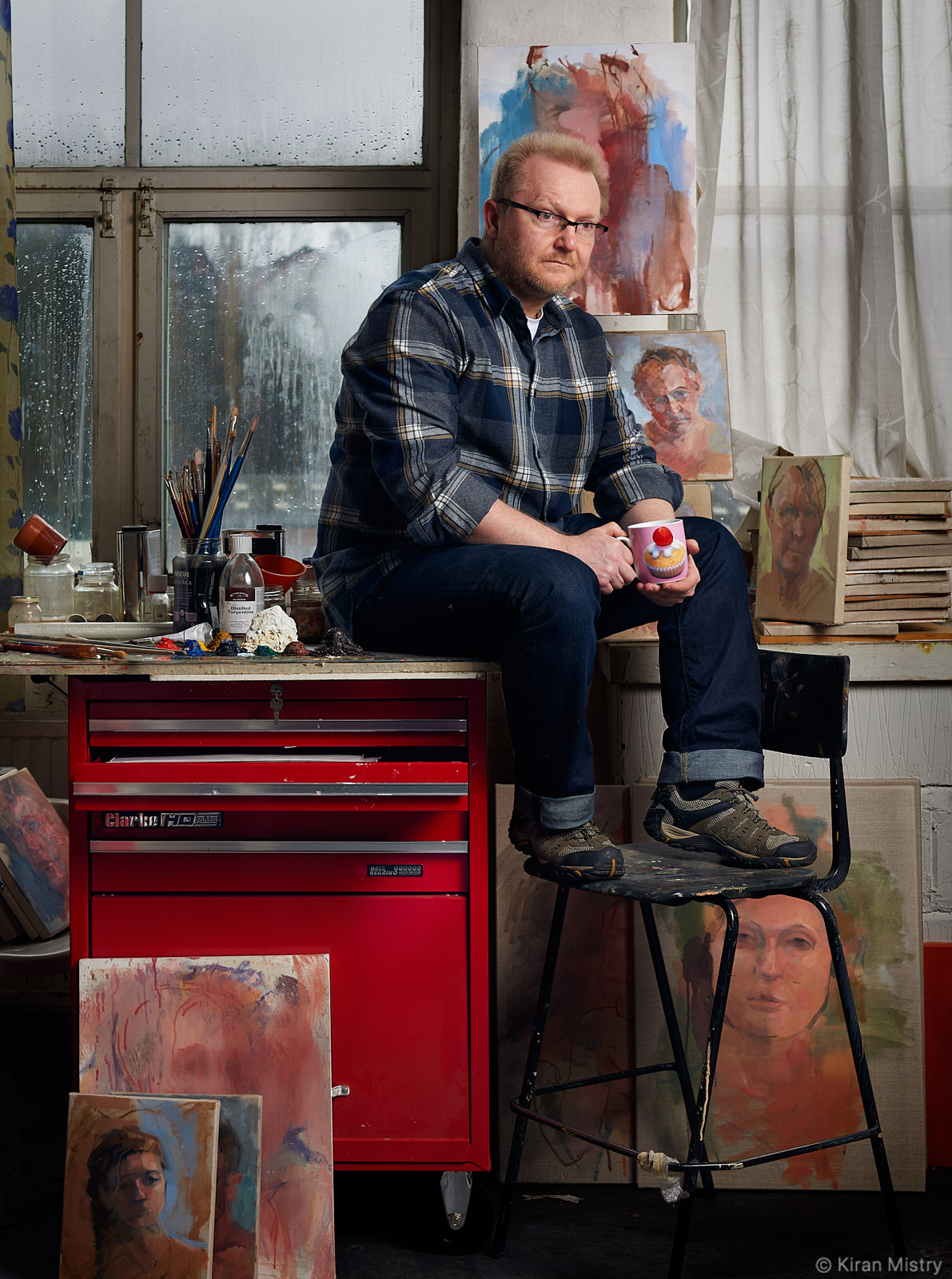 Portrait of artist Andrew Parker in studio surrounded by paintings