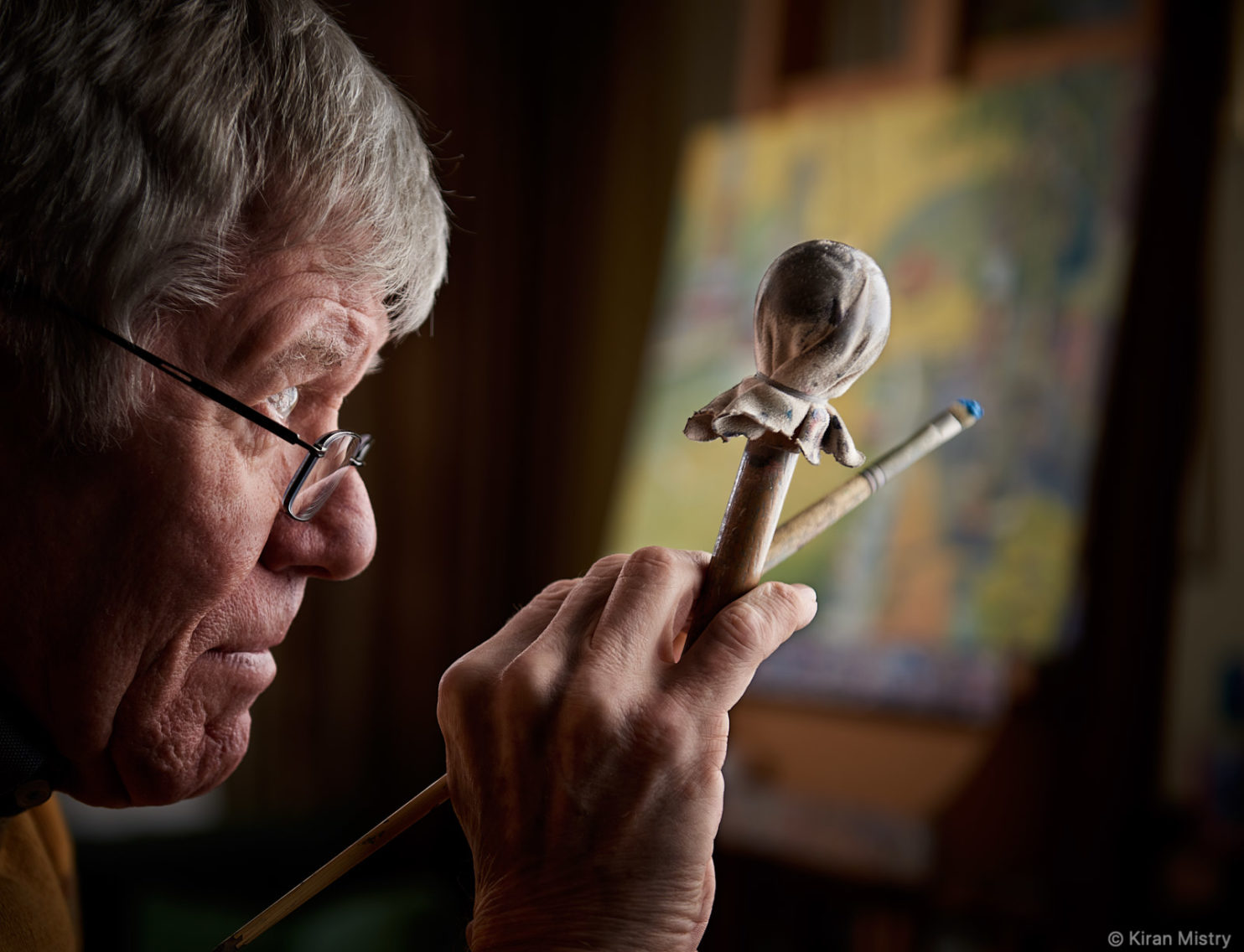 Profile portrait of artist Cliff Murphy holding a Maulstick
