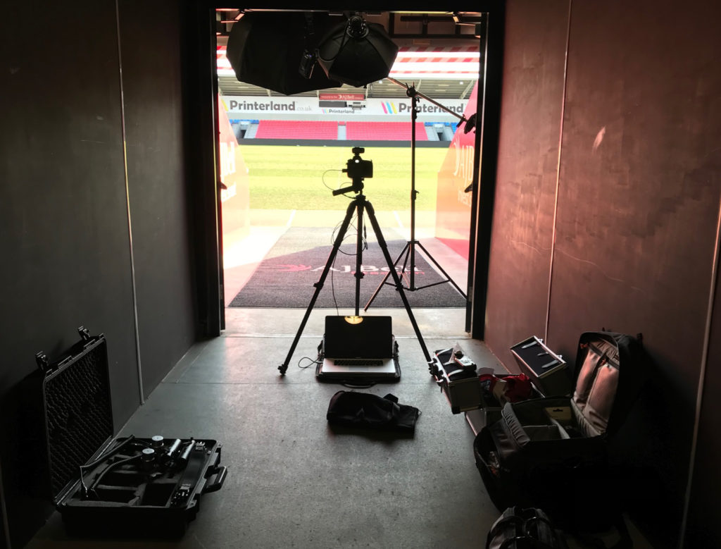A behind the scenes look at the cameras and lighting gear used to photograph a rugby stadium image.