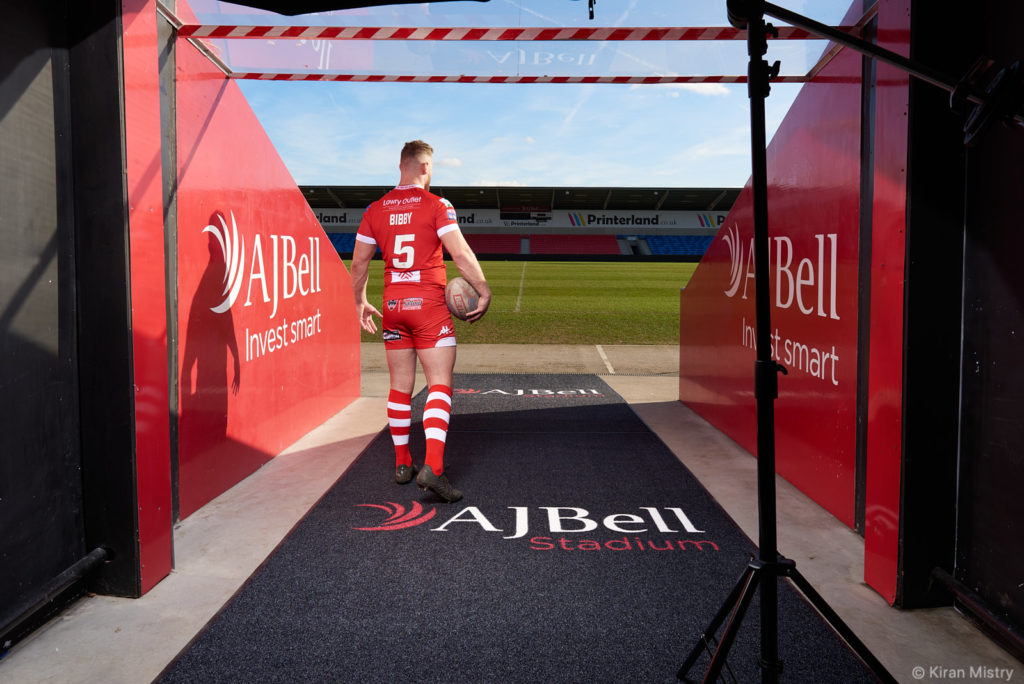 A rugby player holding a ball walking out of the players tunnel towards the pitch.