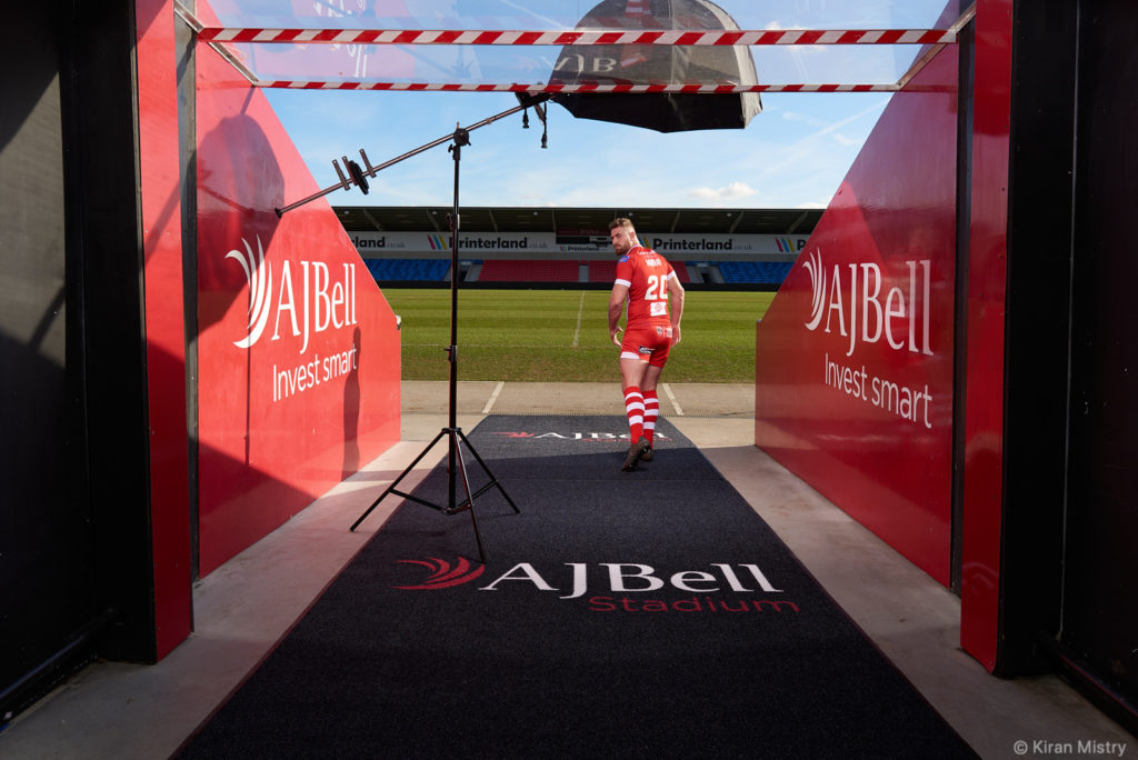 A rugby player model running out of the players tunnel looking back toward camera. With lighting equipment in view.