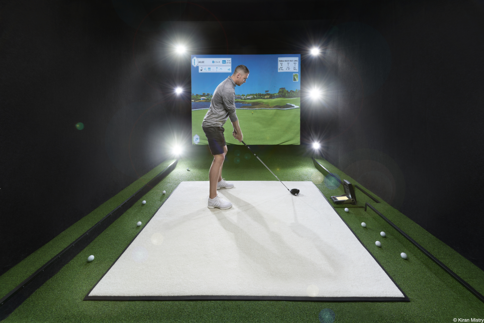 golfer in simultion room standing on a white mat
