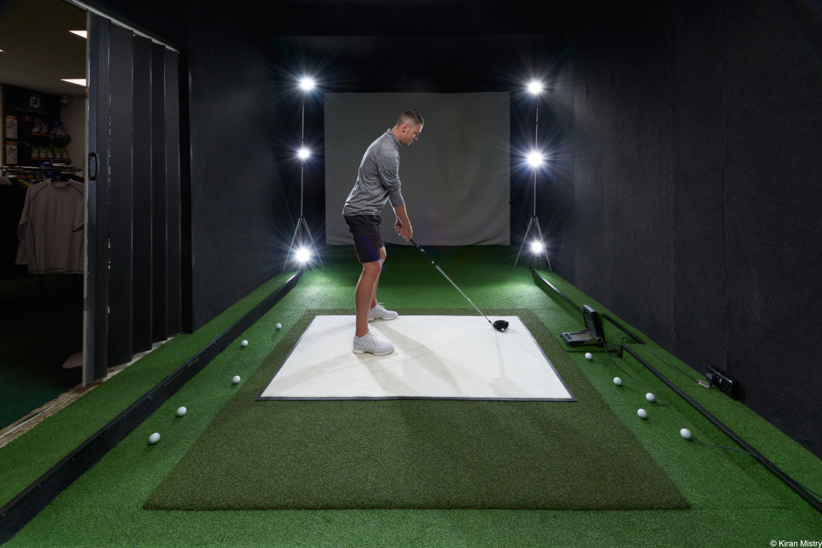 golfer on white mat in a simulation room