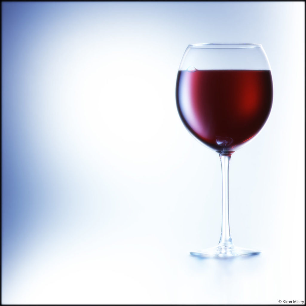 red wine glass with blue background