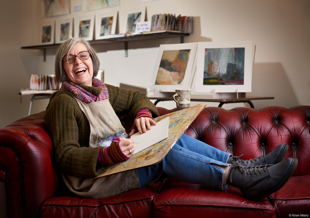Artist Liz Ackerley sitting on a leather red Chesterfield at her studio in Mossley