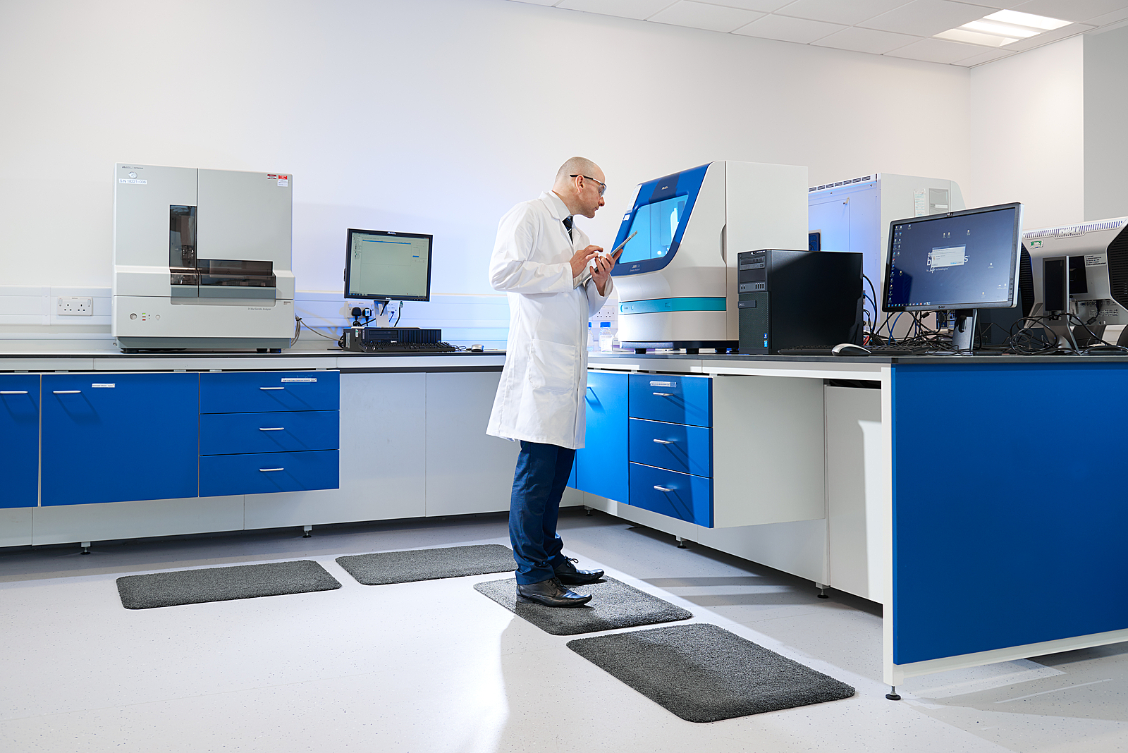 lab technician inspecting machine in lab environment